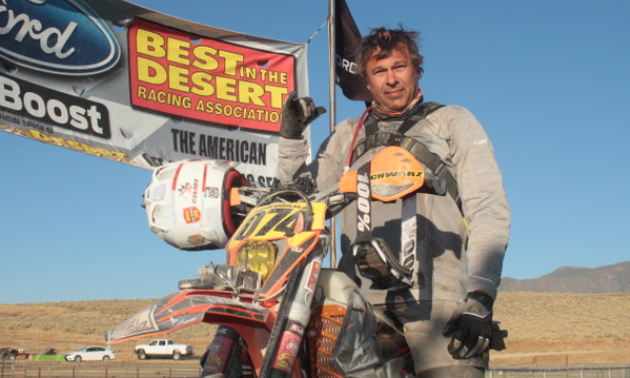Florian Schwarz poses under a banner for the Best in the Desert Vegas to Reno race.