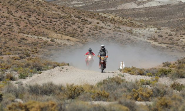 Two motorcycles drive towards the camera on a desert track.