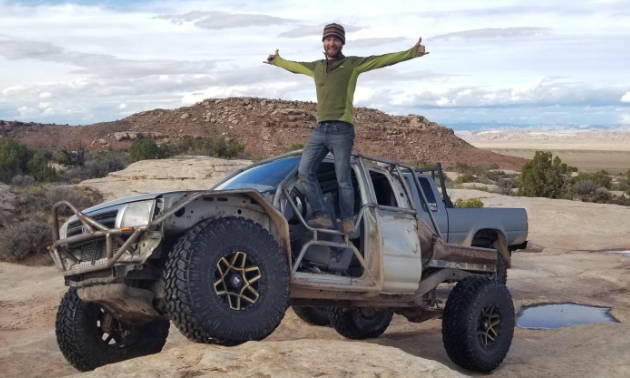 Ethan Schlussler poses with outstretched arms on his rock crawler Toyota Tacoma.