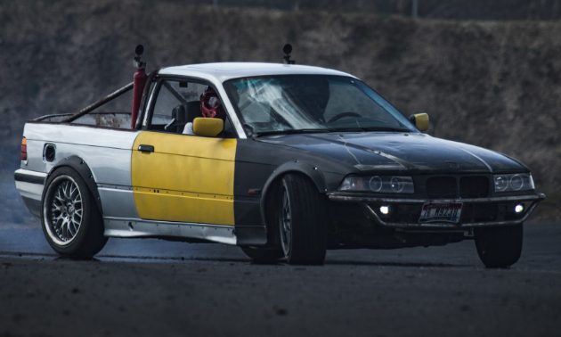 A fully-caged convertible BMW E46 drift car slides on a closed course.