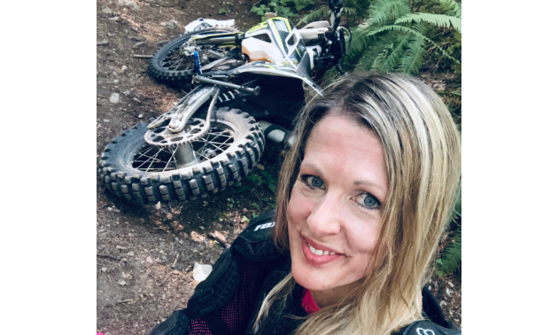 Jennifer Boulet smiles for a selfie with her dirt bike laying down behind her.