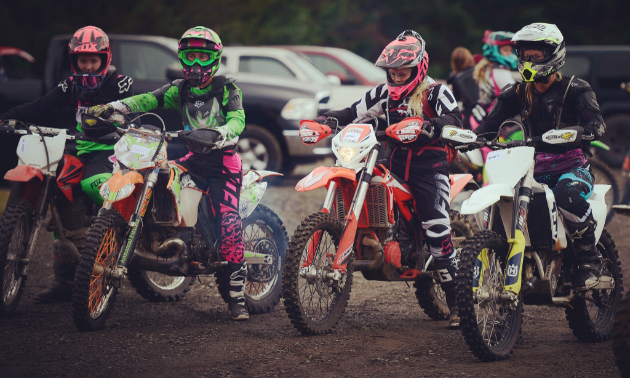 A row of four dirt bikers lined up next to each other.
