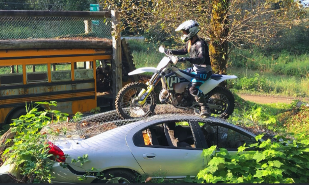 A dirt biker on top of a grey car in an enduro park. There is a school bus and tree in the background.