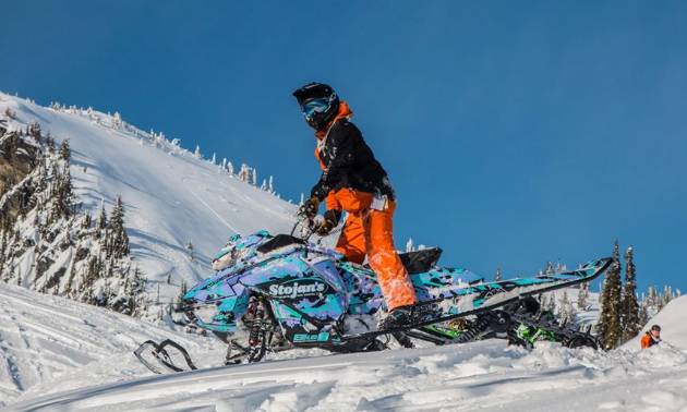 A man in orange pants stands up at the controls of a turquoise and purple snowmobile.