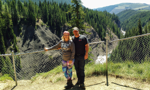 Jody Stevens and her husband, John, stand in front of a fence with Elkford's mountains in the background.