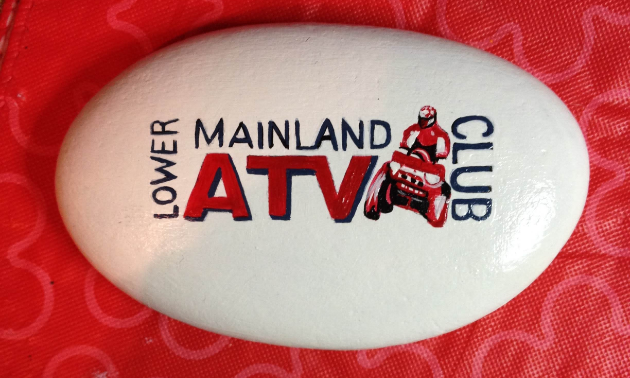 A painted rock of the Lower Mainland ATV Club's logo.