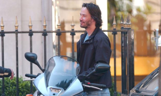 Keanu Reeves smiles as he prepares to ride his motorcycle.