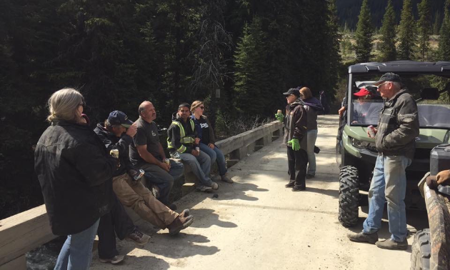 People sit on the edge of a bridge next to an ATV.