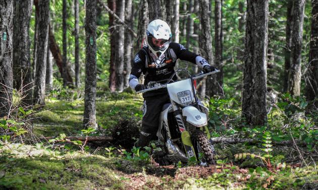Kitt Stringer riding a dirt bike in a dense forest at the Kirk