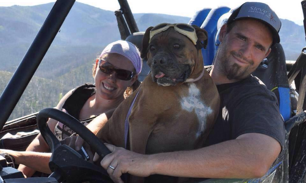Lisa and Nathan Block smile from within their 2015 Polaris 900 RZR while their boxer Brooklyn sits on Nathan's lap.