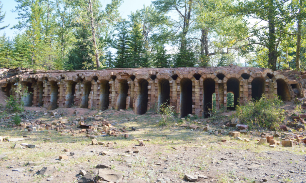 Dilapidated coke ovens have narrow arches between slits of bricks.