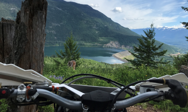 A beautiful view of mountains and a lake from behind the handlebars of a dirt bike.