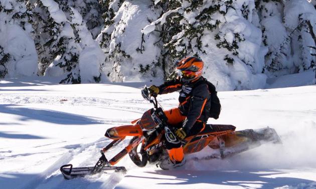 An orange snow bike carves through a white glade.