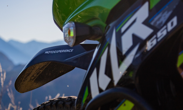 A close-up shot of a KLR 650 motorcycle with Moto Experience written along the side of the bike.