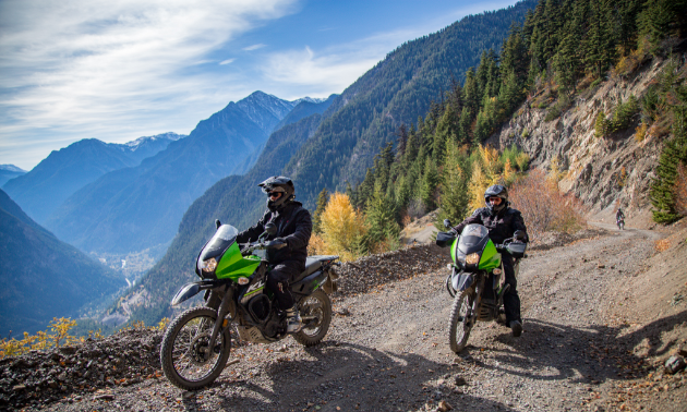 Two motorcyclists make their way up a mountain along a dirt road.