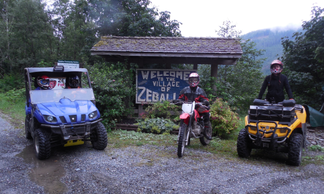 "A side-by-side, dirt bike and quad line up for a photo in front of a ""Welcome to Zeballos"" sign."