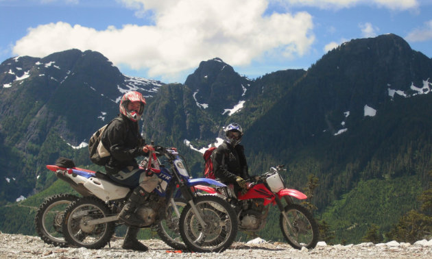 Two motorcyclists pose for a photo in front of towering mountains under a blue sky with few clouds.