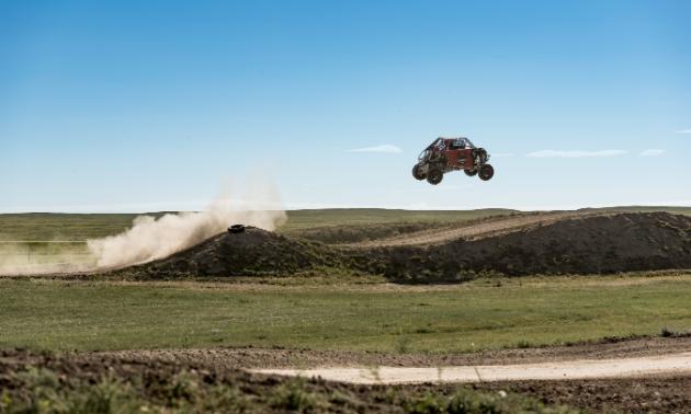 An ATV gets massive air off of a jump.