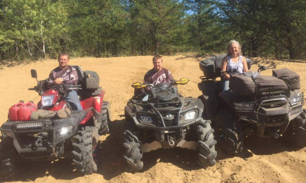 (L to R) Darcy, Ryan and Bernice Ruf are sitting on their three respective quads on a dirt patch with green trees behind them.