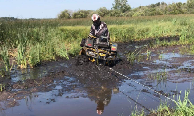 Ryan Ruf is stuck in deep mud. A wench is tied to something out of view to pull his ATV out.