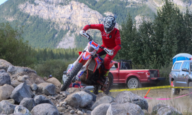 Sam King makes his way across rocky terrain on his motorcycle.