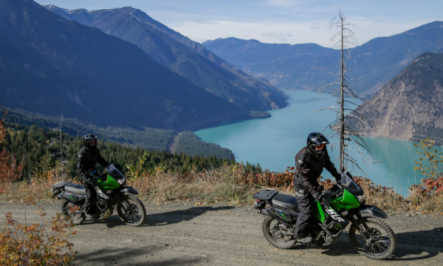 Motorcyclists ride a dirt road above Seton Lake down in a valley between mountains.