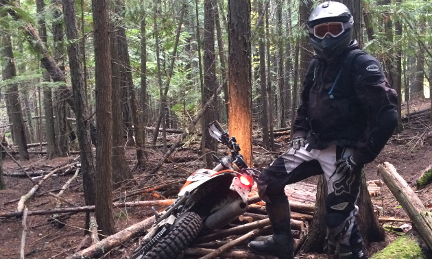 Shawn Handley stands next to his motorcycle in the woods.