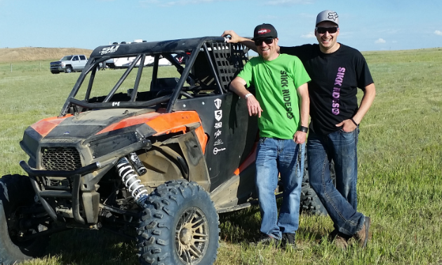 (L to R) Shelden Baynham and Jesse Madlung pose in front of a UTV in Taber, Alberta.