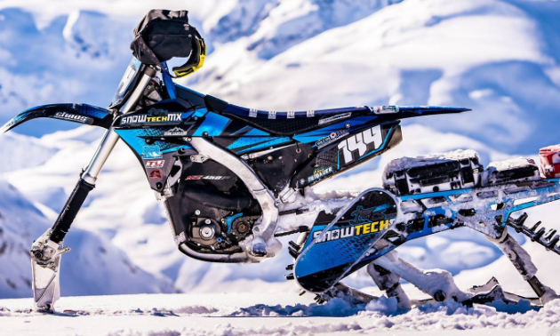 A side profile of a blue and white snow bike with snow-covered mountains in the distance.