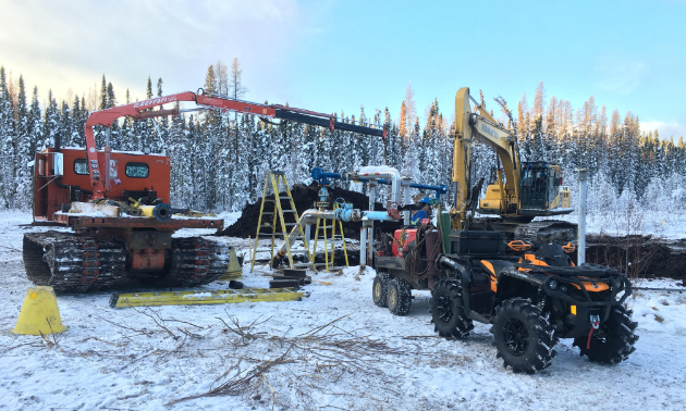 A crane, digger and Travis Hallam's orange 2016 Can-Am Outlander XTP 1000 are parked at a work site during a pipeline dig-up after a recent snowfall.