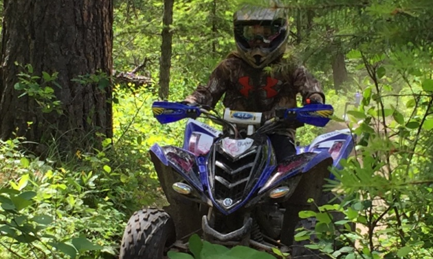 An ATV drives through the woods