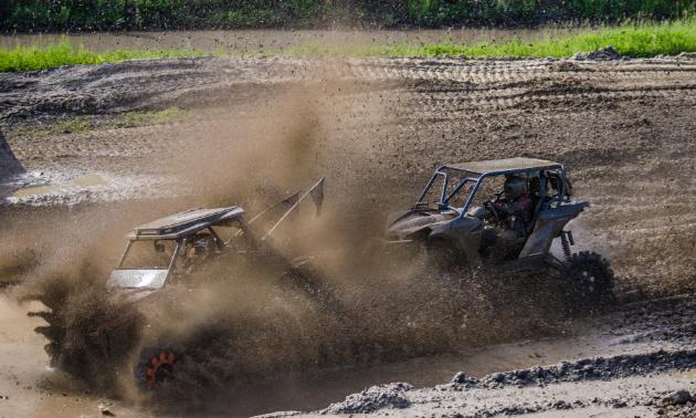ATVs ride through the mud