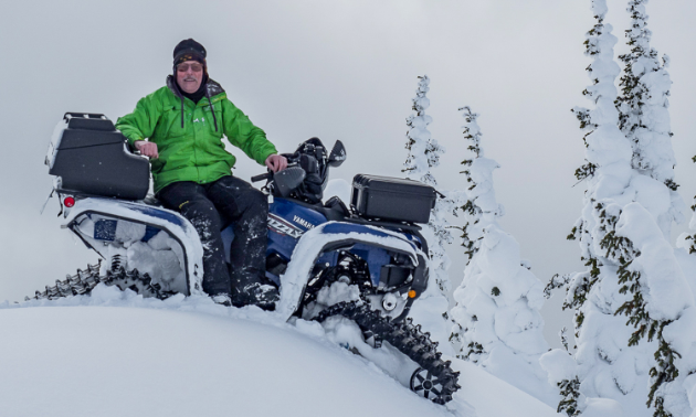 Doug Williamson poses on his ATV with tracks