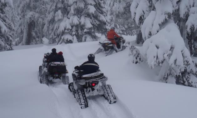 Three ATVs with tracks ride through the snow