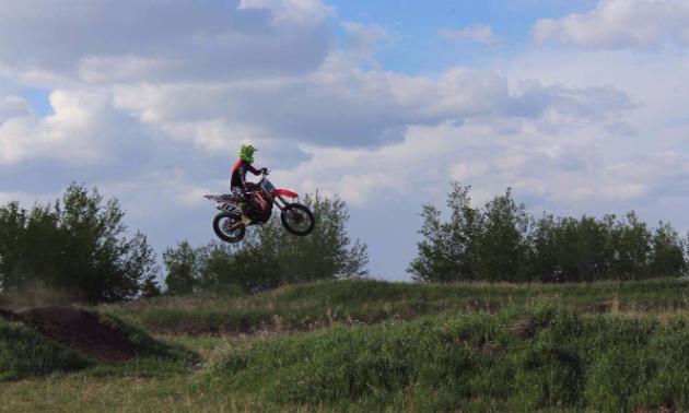 A motorcyclist gets air over a jump