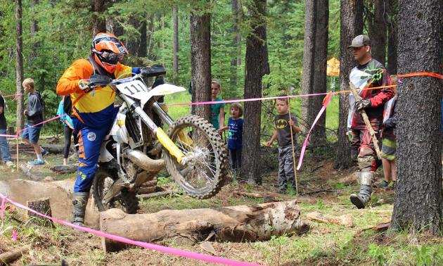 A dirt bike rider drives over deadfall