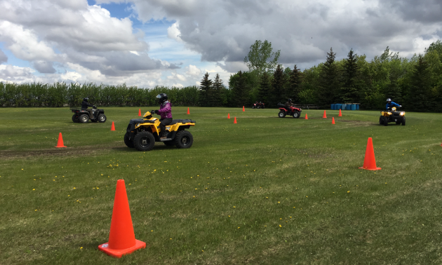 ATVs ride in a field