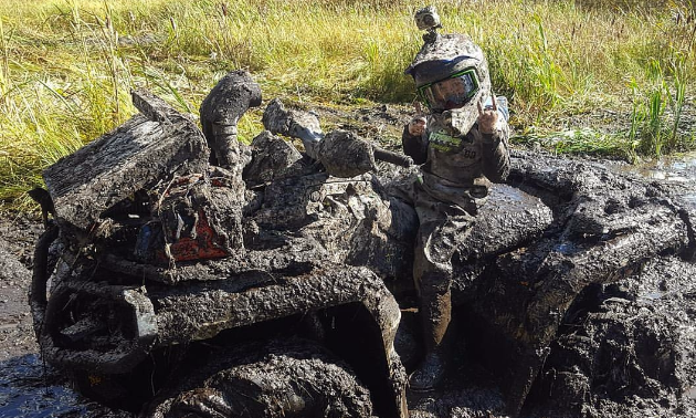 Taigen and his ATV are covered in mud