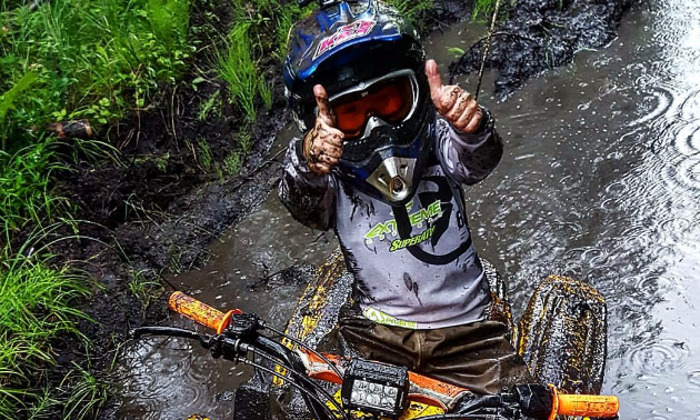 Taigen gives a thumbs up while reading his ATV