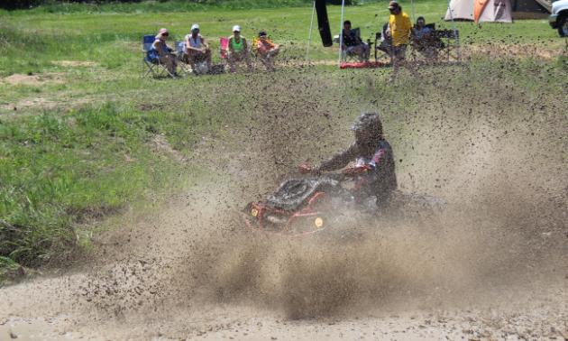 An ATVer rides through the mud