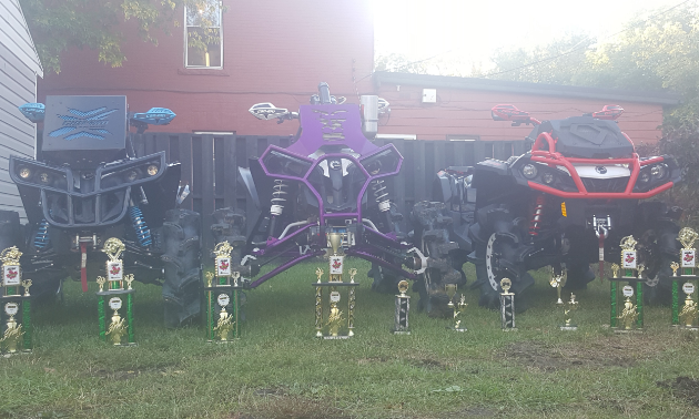 A line of trophies sits in front of 3 ATVs