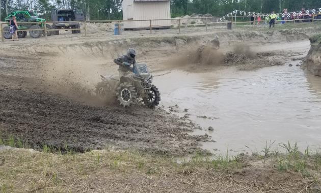 An ATVer rides through a racetrack of mud