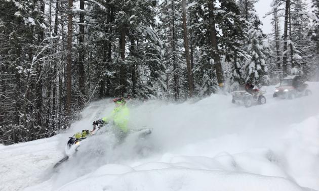 An ATV plows through the snow