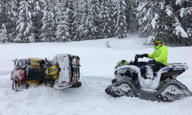 An ATV with treads pulls an ATV that was stuck