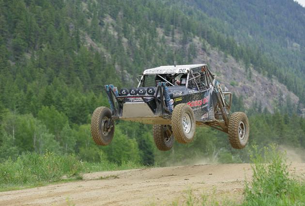 A desert race car flying over a jump.