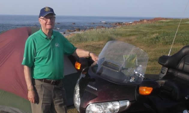 An older man standing next to a motorcycle on a grassy lookout.