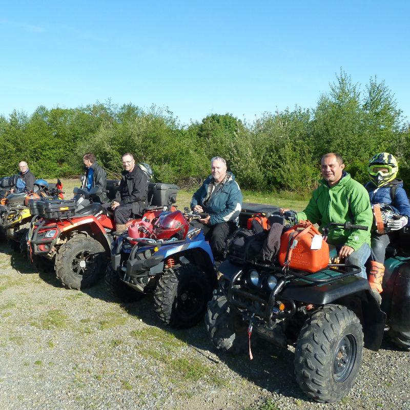 A row of ATVers sit on their rides and pose for a photo.