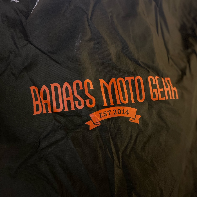 The Badass Moto Gear logo in orange on a black background.