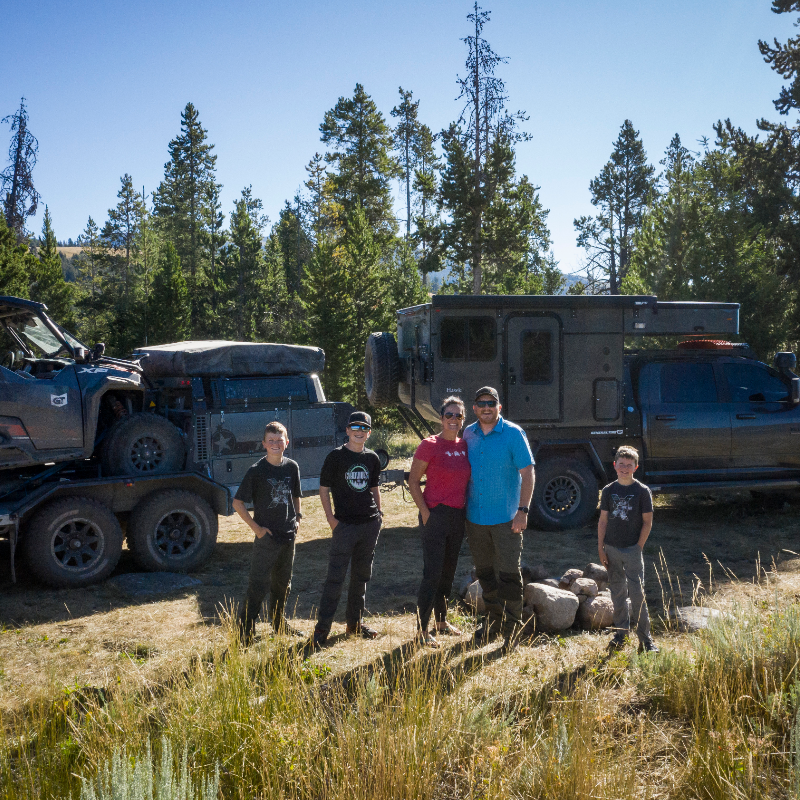 (L to R) Ryder, Cyrus, Rachelle, Clay and Eli Croft stand in front of their Dodge Ram 3500, carrying a Patriot Camper TH610 trailer with a Polaris General 1000.