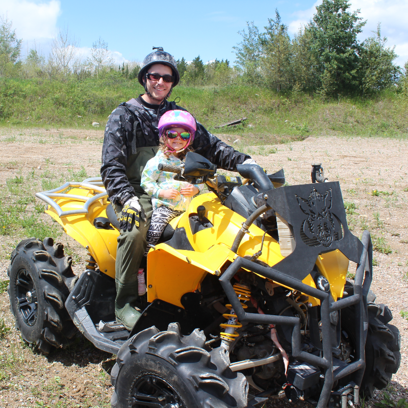 Dan Militere takes his daughter Tess for a ride on a yellow Can-Am ATV.